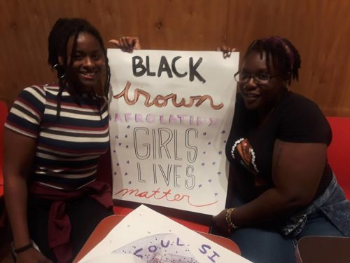 "two members of soul sisters holding a sign that says ""black and brown girls lives matter"""