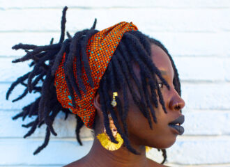 portrait of Alexis standing in front of a white brick wall. Her locs are tied up in a sculptural hairstyle. She is wearing gold earrings and dark lipstick