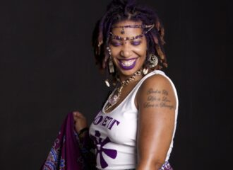 portrait of Jaiye wearing purple african print wrap dress, jewelry, and with cool makeup and smiling